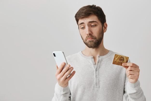 Sombere en droevige kerel die smartphone bekijkt terwijl hij creditcard vasthoudt
