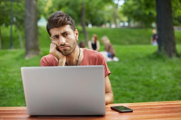 Sombere en verdrietige man zit in park met laptop, op zoek boos
