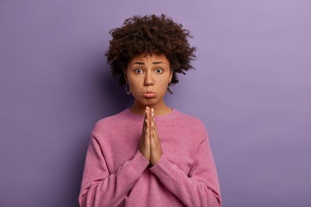 Sombere etnische vrouw grijpt de handen in gebed, snikt en smeekt om gunst, vraagt om geld te lenen, heeft uw hulp nodig in moeilijke situaties, kijkt wanhopig, smeekt, vraagt moeder om excuses
