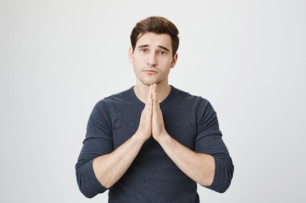 Sombere jongeman verontschuldiging vragen, smekend om genade met de handen in bid