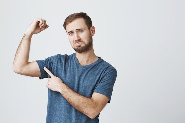 Sombere man die klaagt, biceps buigt en fronst