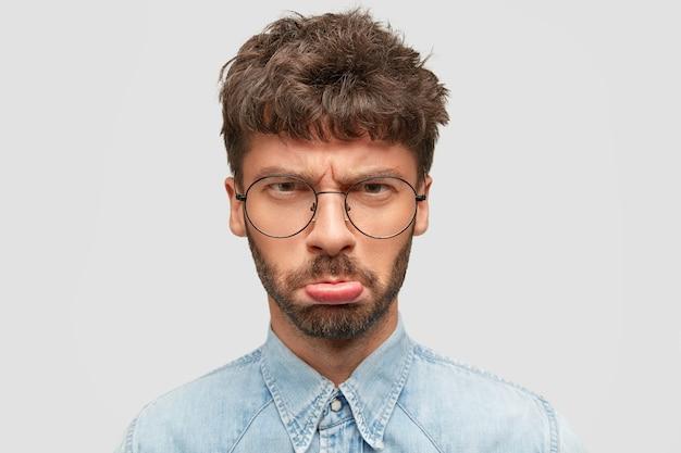 Sombere man met stoppels pakt de lippen en kijkt ontevreden naar de camera, voelt zich beledigd na het horen van slechte woorden die aan hem gericht zijn, draagt een spijkerblouse