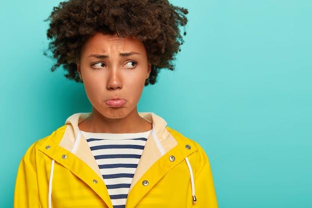 Sombere, medelijdende vrouw met krullend kapsel, fronsend boos gezichtsuitdrukking, portemonnees lippen en kijkt opzij, staat ongelukkig binnen, slecht humeur tijdens regenachtige dag, heeft picknick verwend