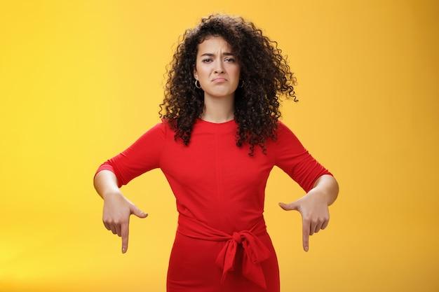 Sombere, schattige, domme, krullende vrouw in een rode jurk fronsend van streek en maakt een droevige glimlach terwijl ze naar beneden wijst met spijt en ontevreden uitdrukking, jaloers of ontevreden over de gele muur.