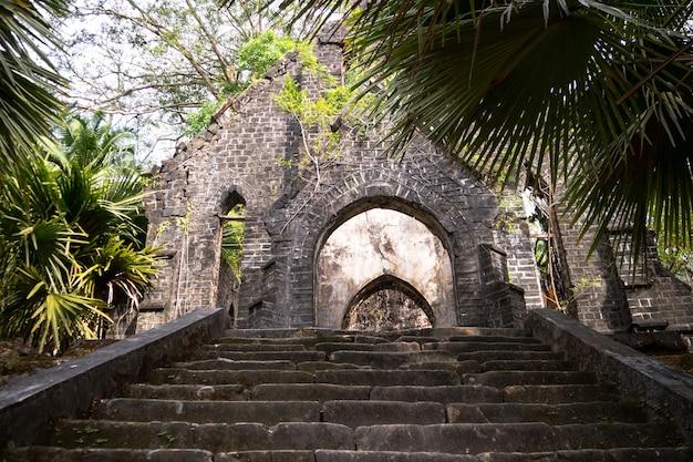 Sombere stenen trap in de jungle. oude presbyteriaanse kerkruïnes ross island, port blair, andaman en nicobar india. de oude verlaten trap. ingang van het verlaten gebouw. vervallen huis