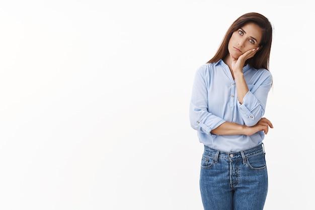 Sombere trieste blanke vrouwelijke huisvrouw verontrust, staat ongemakkelijk leun op getatoeëerde hand, ziet er geïrriteerd moe uit, uitgeput tot laat werkend, staart verveeld onverschillig naar voren, staat geïrriteerde witte muur