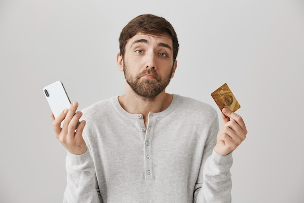 Sombere trieste man schouderophalend, met creditcard en mobiele telefoon