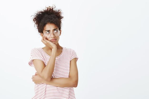 Sombere vrouw met afro kapsel poseren in de studio
