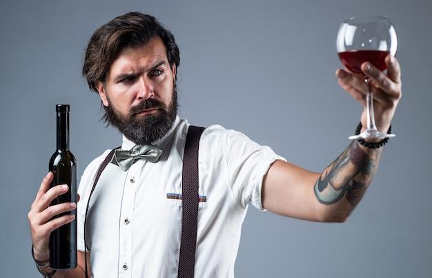 Sommelier die alcohol proeft. bebaarde man in bretels drinkt rode wijn. brutale man barman in vlinderdas. elegante mannelijke barman. knappe hipster wijnglas drinken. selectieve aandacht.