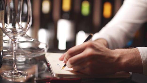 Sommelier houdt aantekeningen in een notitieboek tegen de achtergrond van planken met wijnflessen. close - up van handen