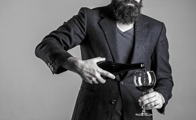 Sommelier man, degustator, wijnmakerij, mannelijke wijnmaker. fles, rode wijnglas. ober gieten rode wijn in een glas. baardman, bebaarde, sommelier, proeverij. rode wijn uit fles gieten in het wijnglas.