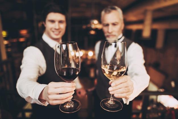 Sommeliers houden glazen rode en witte wijn vast.