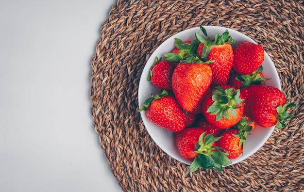 Sommige aardbeien in een kom op onderzetter en witte achtergrond, hoogste mening.