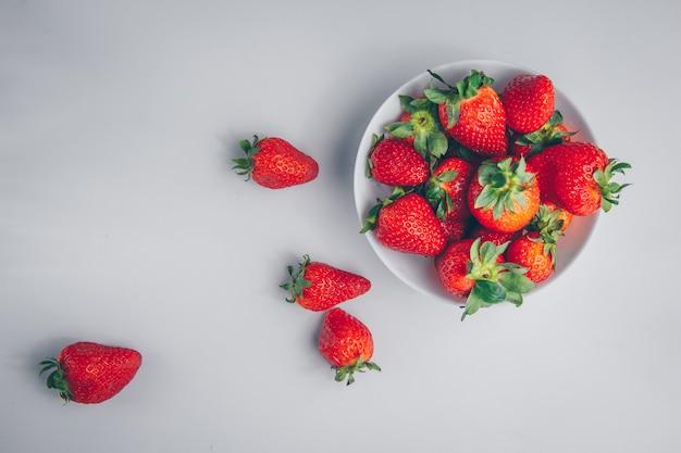 Sommige aardbeien in een kom op witte achtergrond, bovenaanzicht.