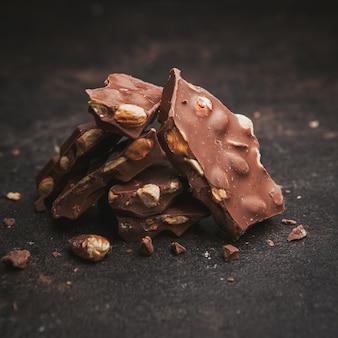 Sommige amandelen met chocolade op donkerbruin geweven, close-up.