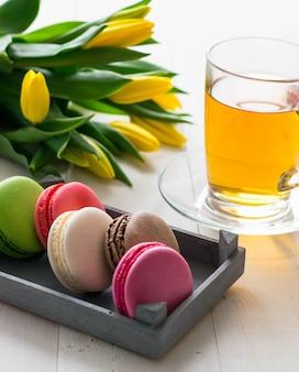 Sommige bitterkoekjes, tulpen en kopje thee op de houten tafel