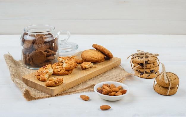 Sommige bruine koekjes met amandelen in een kom, koekjes op een snijplank en een stuk zak in een glazen pot op witte ondergrond