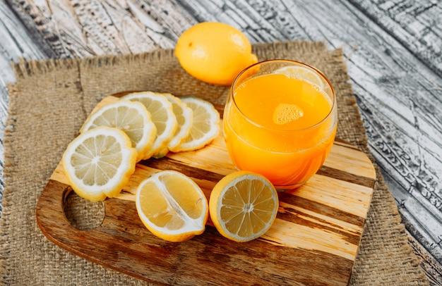 Sommige citroenen met plakjes en sap op snijplank, doek en houten achtergrond, hoge hoek bekijken.