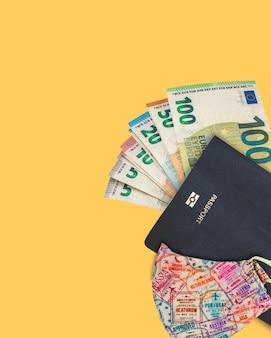 Sommige eurobankbiljetten met een covid-masker en een paspoort.