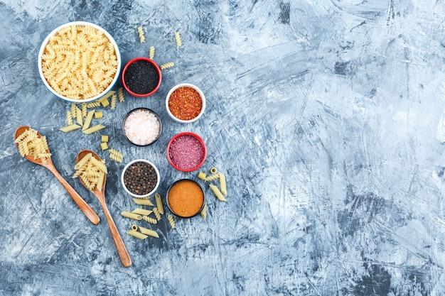 Sommige fusilli pasta met kruiden in kom en houten lepels op grijze gips achtergrond, bovenaanzicht.