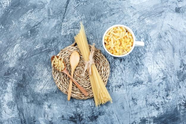 Sommige geassorteerde pasta met houten lepels in kom op grijze gips en rieten placemat achtergrond, bovenaanzicht.