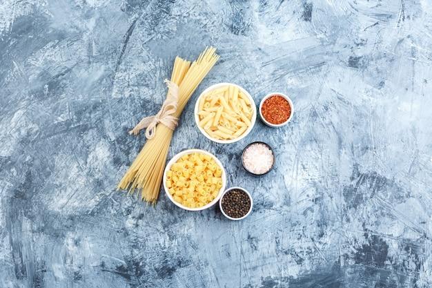 Sommige geassorteerde pasta met kruiden in kommen op grijze gips achtergrond, bovenaanzicht.