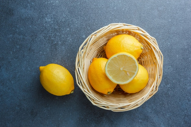 Sommige gele citroenen in een mand op donkere ondergrond, bovenaanzicht.