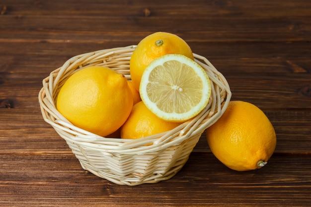 Sommige gele citroenen met gesneden citroen in een mand op houten oppervlakte, hoge hoekmening.
