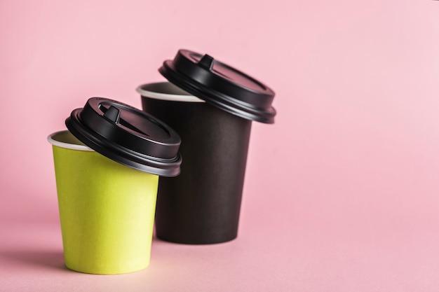 Sommige groene en zwarte papieren herbruikbare koffiekopjes met deksels.