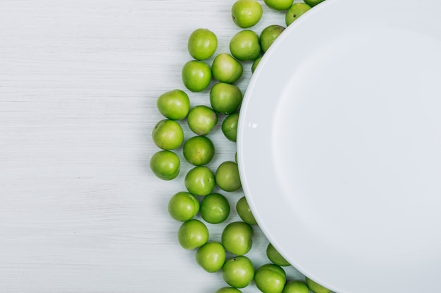 Sommige groene kersenpruimen met lege plaat op witte houten achtergrond, close-up. kopieer ruimte voor tekst