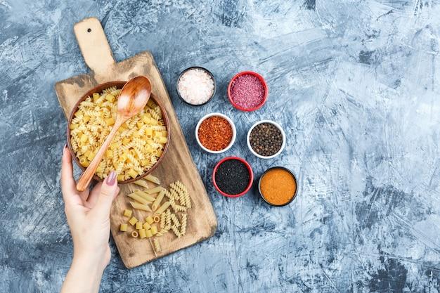 Sommige hand met kom pasta met kruiden, houten lepel op grijze gips en snijplank achtergrond, bovenaanzicht.