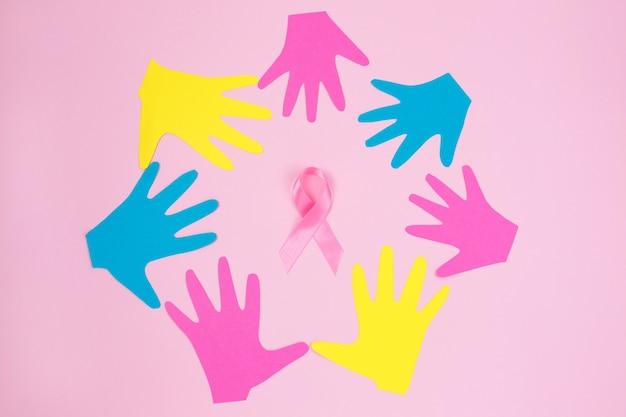 Sommige handafdrukken van verschillende kleuren vormen binnen een cirkel en een roze lint