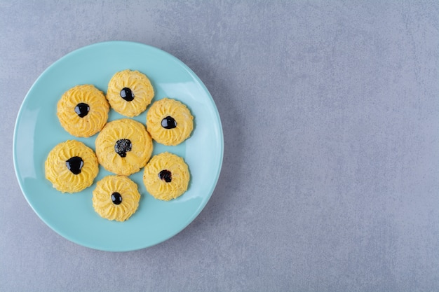 Sommige heerlijke gele koekjes met chocoladesiroop op een blauw bord.
