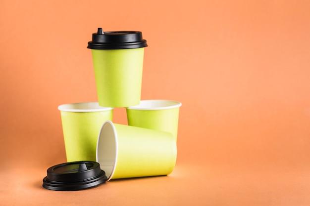 Sommige herbruikbare koffiekopjes van groen papier met een gesloten zwart deksel.