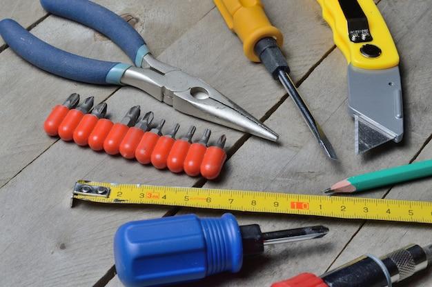 Sommige huisreparatietools liggen op een houten ondergrond. detailopname. Premium Foto