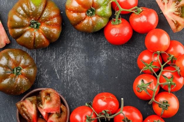 Sommige kleurrijke tomaten met kille tomaten op donkere stenen muur, plat lag. kopieer ruimte voor tekst