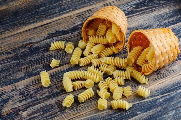 Sommige macaroni die uit kleine emmers op donkere houten achtergrond komen, hoge hoekmening.