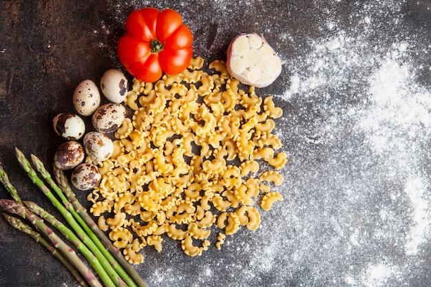 Sommige macaroni met eieren, tomaat, asperges en knoflook op donkere gestructureerde achtergrond, bovenaanzicht.
