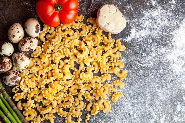 Sommige macaroni met eieren, tomaat en knoflook op donkere gestructureerde achtergrond, bovenaanzicht.