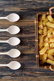 Sommige macaronideegwaren met lepels in een dienblad op houten achtergrond, hoogste mening.