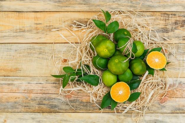 Sommige mandarijnen met bladeren op een houten bord