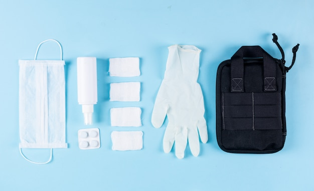 Sommige medische handschoenen met handtas, masker, verbanden, spray opgesteld op lichte cyaan achtergrond, bovenaanzicht.