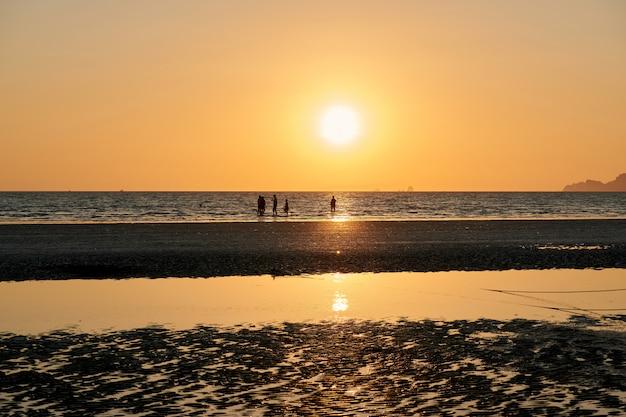 Sommige mensen zijn op een strand tijdens zonsondergang