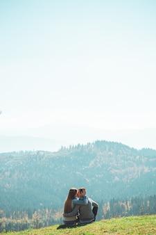 Sommige paar reizigers jongens en meisjes zittend op een klif ontspannende bergen en wolken luchtfoto liefde en reizen gelukkig emoties levensstijl concept.