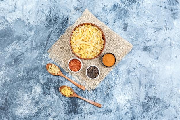 Sommige rauwe pasta met kruiden in kom en houten lepels op gips en stuk zak achtergrond, bovenaanzicht.
