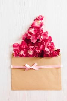 Sommige rode rozenblaadjes in envelop op rood