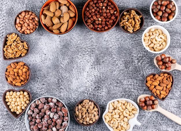 Sommige van geassorteerde noten in een mini verschillende kommen op zwarte stenen tafel