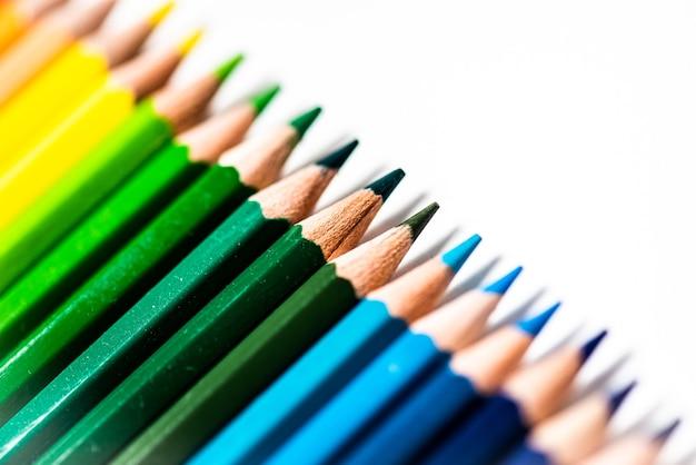 Sommige verschillende gekleurde houten potloodkrijtjes die in een rij voor een witte geïsoleerde achtergrond worden geplaatst