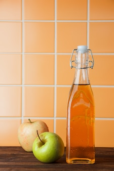 Sommige verse appels met appelsap in een mand op oranje tegelachtergrond, zijaanzicht. ruimte voor tekst