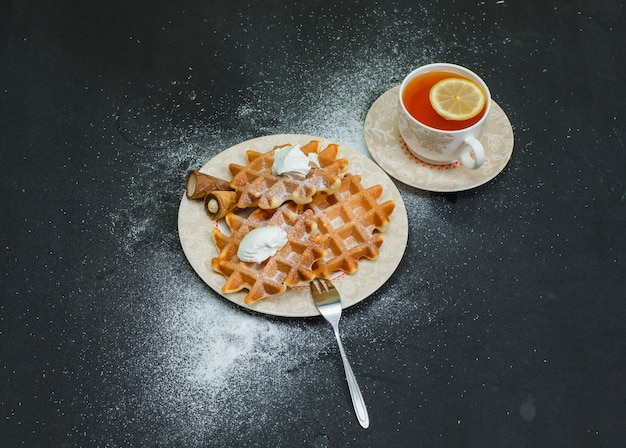 Sommige wafels met thee in een plaat op donkere, hoge hoekmening.